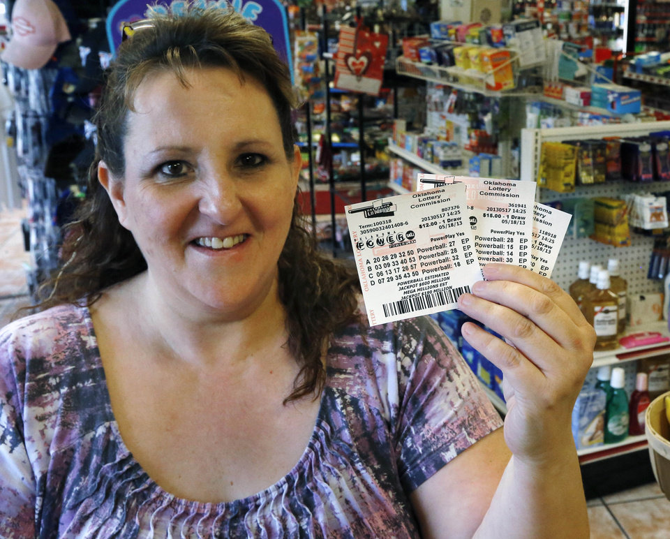 Photo - Cathy Raymond, of Oklahoma City, displays the Powerball Lottery tickets she purchased in Oklahoma City, Friday, May 17, 2013. Powerball officials say the jackpot has climbed to an estimated $600 million, making it the largest prize in the game's history and the world's second largest lottery prize.(AP Photo/Sue Ogrocki)