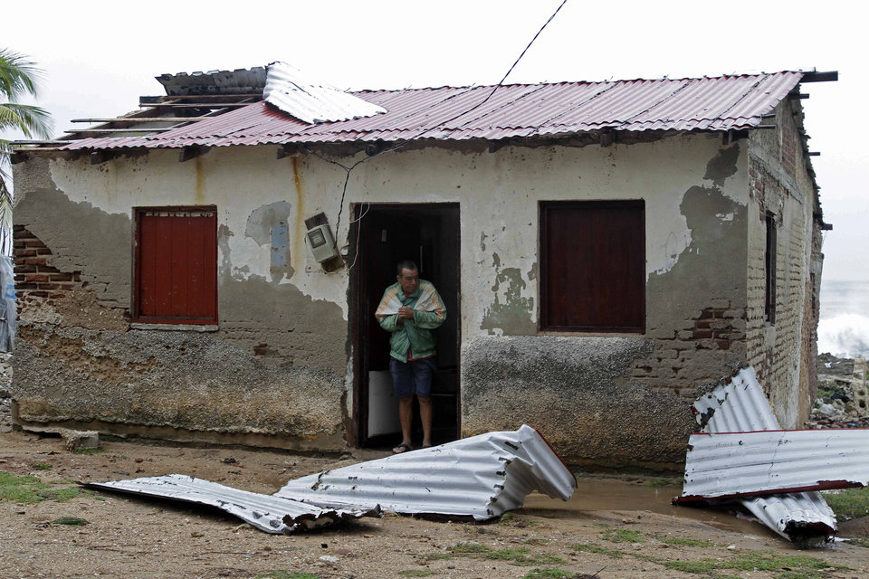 Photo -   Nelson Carballosa stands in his home's doorway after the passing hurricane Sandy damaged his roof in Gibara, Cuba, Thursday, Oct. 25, 2012. Hurricane Sandy blasted across eastern Cuba on Thursday as a potent Category 2 storm and headed for the Bahamas after causing at least two deaths in the Caribbean. (AP Photo/Franklin Reyes)
