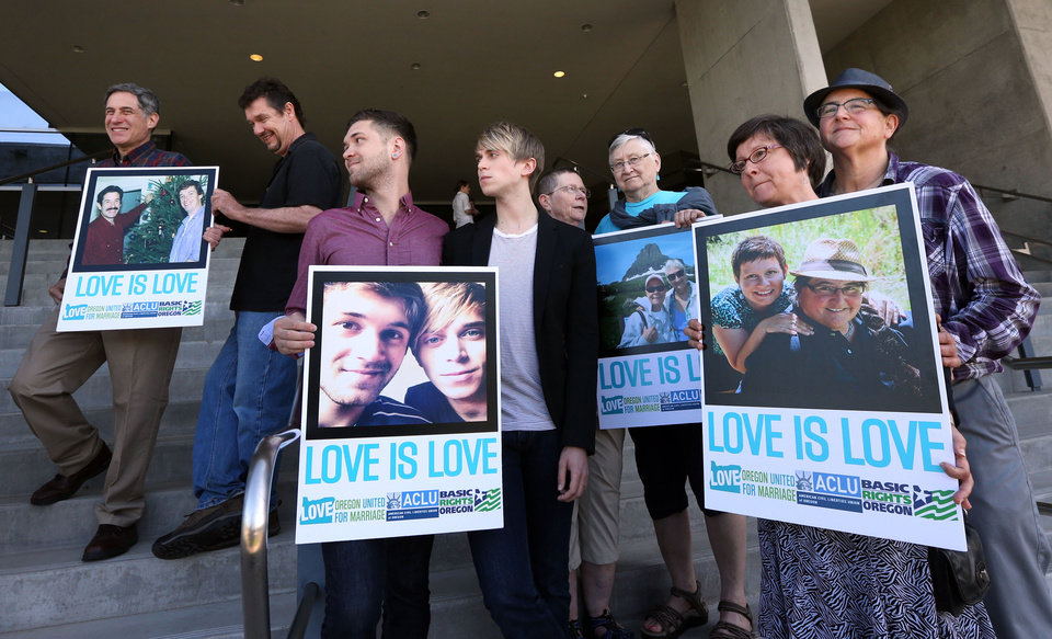Photo - Supporters of same-sex marriage hold photos of themselves and their family members or partners on the steps of the Wayne L Morse U.S. Courthouse Wednesday, May 14, 2014, in Eugene, Ore. A federal judge will hear arguments Wednesday about whether a national group can defend Oregon's ban on same-sex marriage because the state's attorney general has refused to do so. (AP Photo/The Register-Guard, Chris Pietsch)