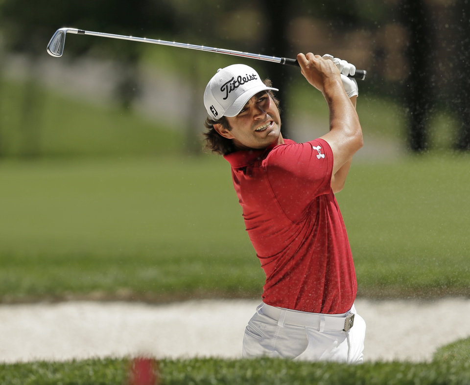 Photo - Martin Flores watches his shot from a sand trap on the fourth hole during the final round of the Wells Fargo Championship golf tournament in Charlotte, N.C., Sunday, May 4, 2014. (AP Photo/Chuck Burton)