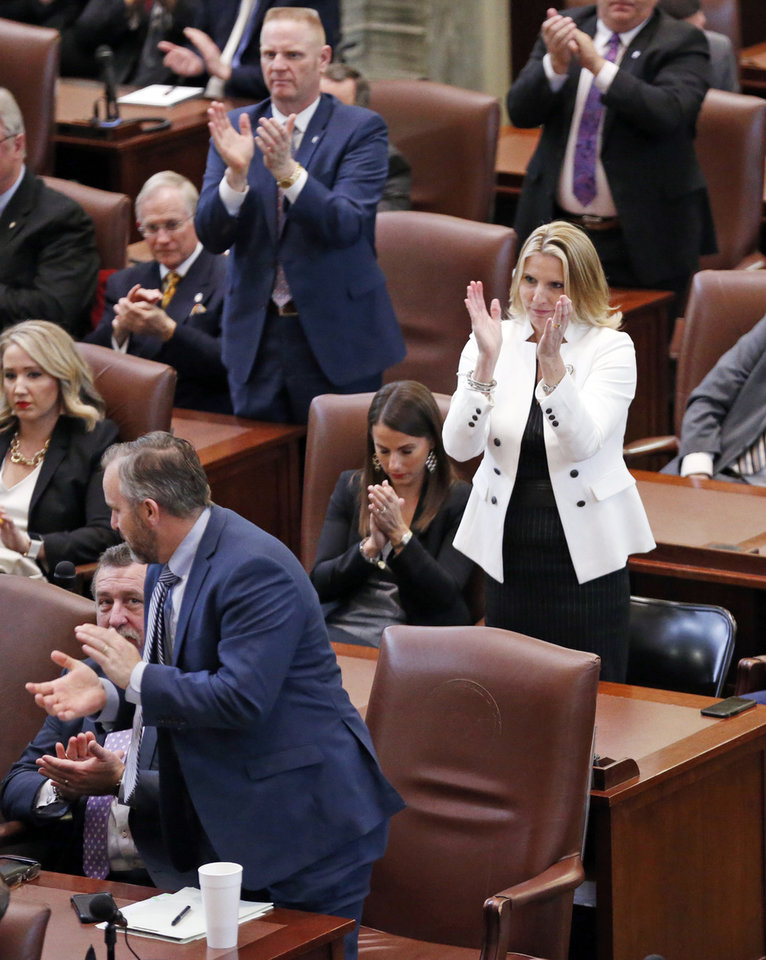 Photo - State Senator AJ Griffin (white coat) applauds a point on mental health as Oklahoma Governor Mary Fallin gives her final State of the State Address in the chambers of the Oklahoma House of Representatives on Monday, Feb. 5, 2018 in Oklahoma City, Okla.  Photo by Steve Sisney, The Oklahoman