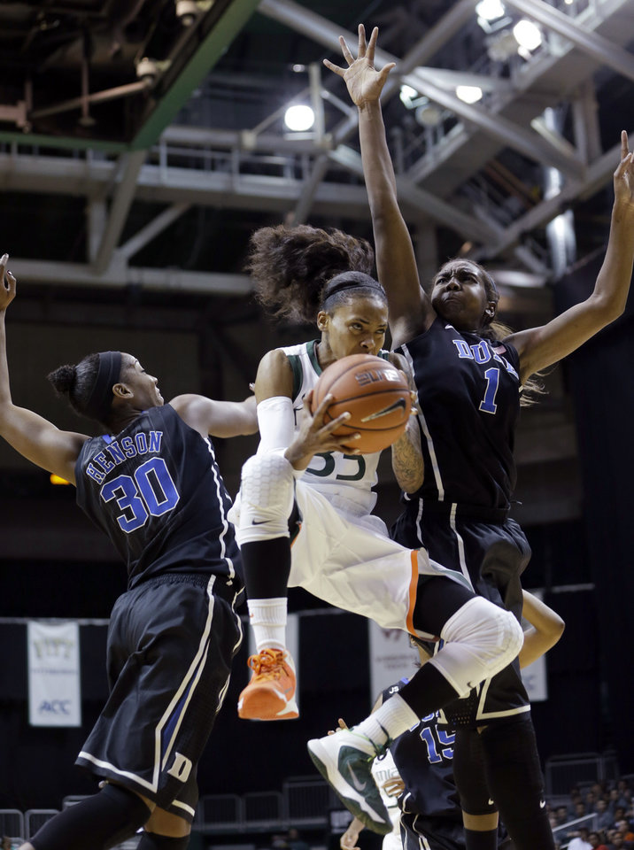 Photo - Miami Hurricanes guard Suriya McGuire (33) goes to the basket as Duke Blue Devils forward/center Amber Henson (30) and forward/center Elizabeth Williams (1) defend during the first half of an NCAA college basketball game in Coral Gables, Fla., Thursday, Jan. 30, 2014. (AP Photo)