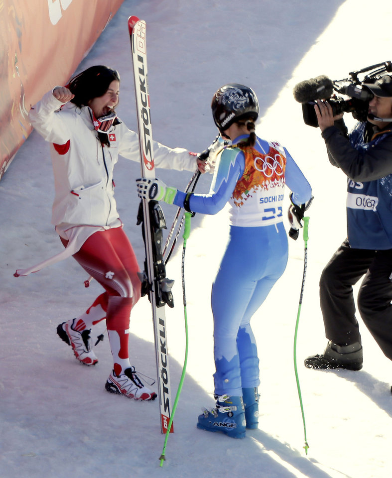 Photo - Gold medalists Slovenia's Tina Maze, right, and Switzerland's Dominique Gisin celebrates after Maze's  run in the women's downhill at the 2014 Winter Olympics, Wednesday, Feb. 12, 2014, in Krasnaya Polyana, Russia. (AP Photo/Charlie Riedel)