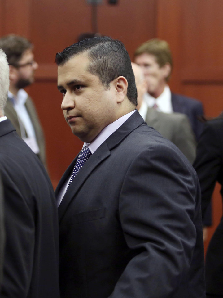 Photo - George Zimmerman leaves court with his family after the jury delivered a not guilty verdict in his trial in Seminole Circuit Court in Sanford, Fla. Saturday, July 13, 2013. Zimmerman was charged with second-degree murder for the 2012 shooting death of Trayvon Martin. (AP Photo/Orlando Sentinel, Gary W. Green, Pool) ORG XMIT: FLJR236