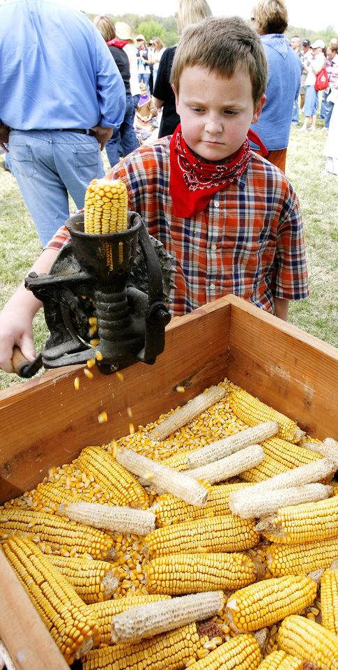 Photo - RE-ENACT / RE-ENACTMENT: Josh Bruza, 9, tries out a corn shucker as third-graders from Chisholm Elementary School participate in land run activities in Oklahoma City Friday, April 24, 2009. Chisholm is in the Edmond Public School District. Photo by Paul B. Southerland, The Oklahoman ORG XMIT: KOD