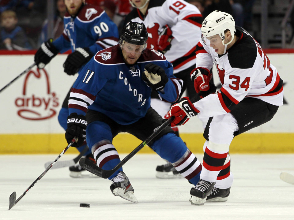 Photo - Colorado Avalanche left wing Jamie McGinn, left, fights for control of the puck with New Jersey Devils defenseman Jon Merrill in the second period of an NHL hockey game in Denver, Thursday, Jan. 16, 2014. (AP Photo/David Zalubowski)
