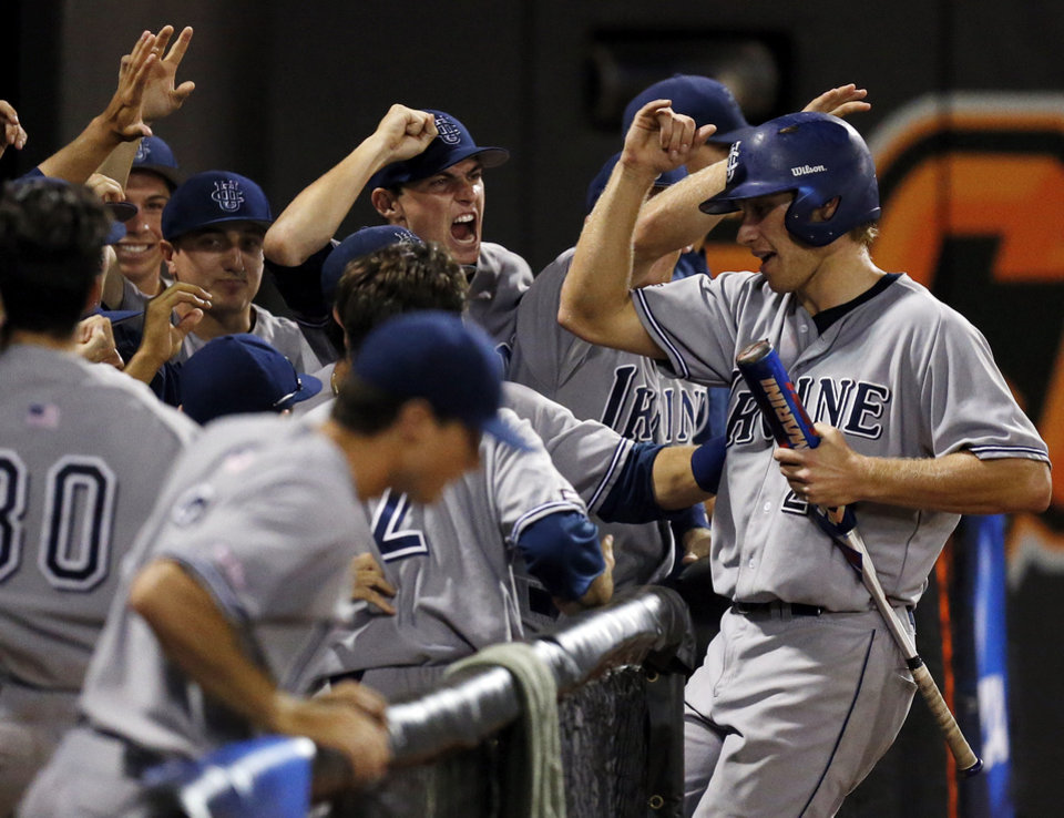 Photo - UC Irvine celebrates a score by Taylor Sparks (25) in the 5th inning during Game 1 of the NCAA baseball Stillwater Super Regional between Oklahoma State and UC Irvine at Allie P. Reynolds Stadium in Stillwater, Okla., Friday, June 6, 2014. Photo by Nate Billings, The Oklahoman