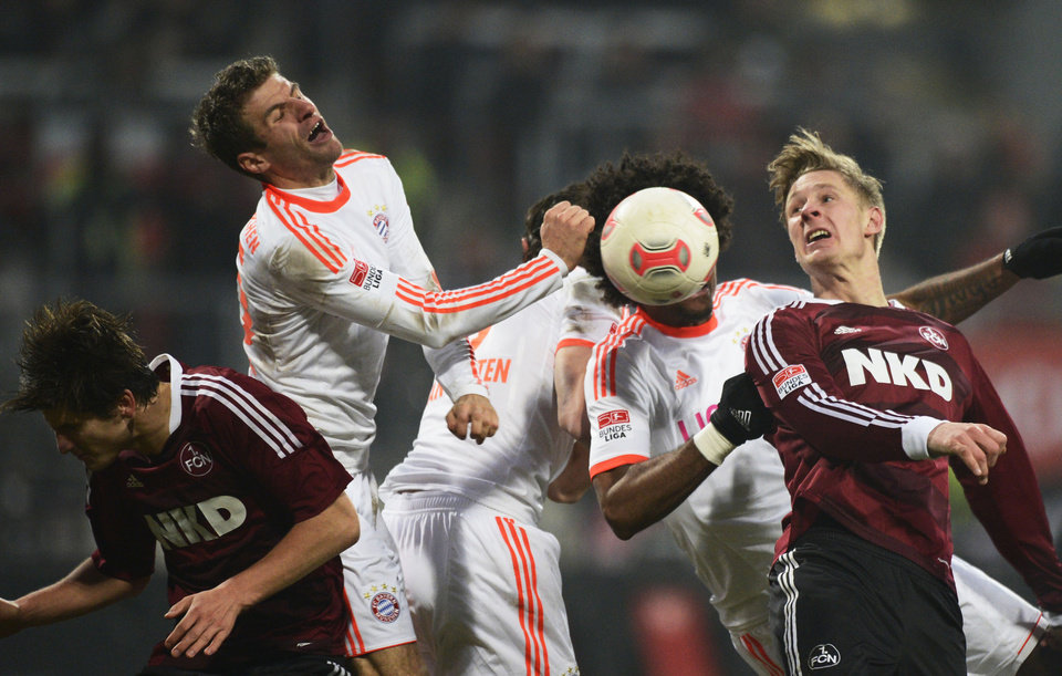 Photo -   Munich's Thomas Mueller, second left, and Dante, second right, challenge with Nuremberg's Sebastian Polter , right, during the German Bundesliga soccer match between 1. FC Nuremberg and FC Bayern Munich in Nuremberg, southern Germany, Saturday Nov. 17, 2012. (AP Photo/dapd/Sebastian Widmann)