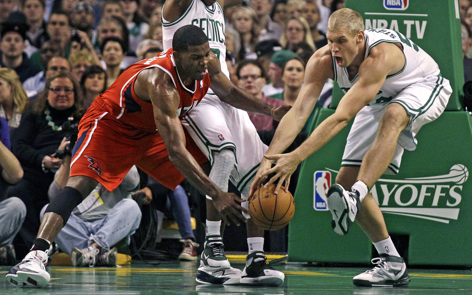 Boston Celtics center Greg Stiemsma, right, reaches for the loose ball against Atlanta Hawks guard Joe Johnson (2) during the first quarter of Game 3 of an NBA first-round playoff basketball series, Friday, May 4, 2012, in Boston. (AP Photo/Charles Krupa)