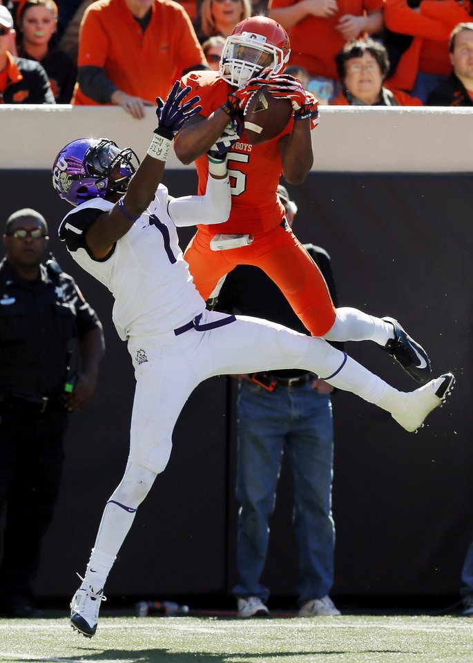 Oklahoma State's Josh Stewart (5) makes a catch over TCU's Chris Hackett (1) on a pass from Charlie Moore (not pictured) in the fourth quarter during a college football game between the Oklahoma State University Cowboys (OSU) and the Texas Christian University Horned Frogs (TCU) at Boone Pickens Stadium in Stillwater, Okla., Saturday, Oct. 19, 2013. OSU won, 24-10. Photo by Nate Billings, The Oklahoman