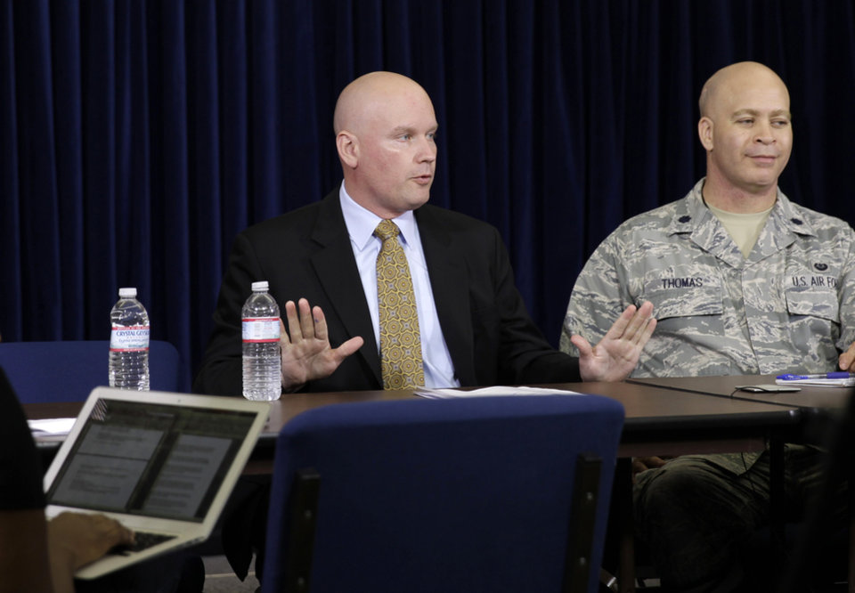 Photo - James Connell, left, the civilian defense lawyer for Ammar al-Baluchi, and Air Force Lt. Col. Sterling Thomas, his military lawyer, speak with reporters about FBI questioning of the defense teams staff in the Sept. 11 war crimes case, on the Guantanamo Bay Naval Base, Cuba, Sunday, June 15, 2014. Lawyers for the defendants say the FBI investigations of defense team staff are part of a pattern of interference in their ability to represent the men that included monitoring on written communications with their clients and the revelation in February 2013 that the rooms in which they meet with clients contained microphones apparently disguised to look like smoke detectors. A judge will consider a delay in the proceedings in a hearing on Monday, June 16. (AP Photo/Ben Fox)