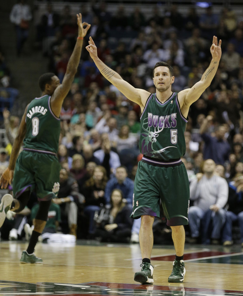 Milwaukee Bucks' J.J. Redick (5) and Larry Sanders, left, react to a three-point basket by teammate Mike Dunleavy against the Atlanta Hawks during the second half of an NBA basketball game, Saturday, Feb. 23, 2013, in Milwaukee. (AP Photo/Jeffrey Phelps)