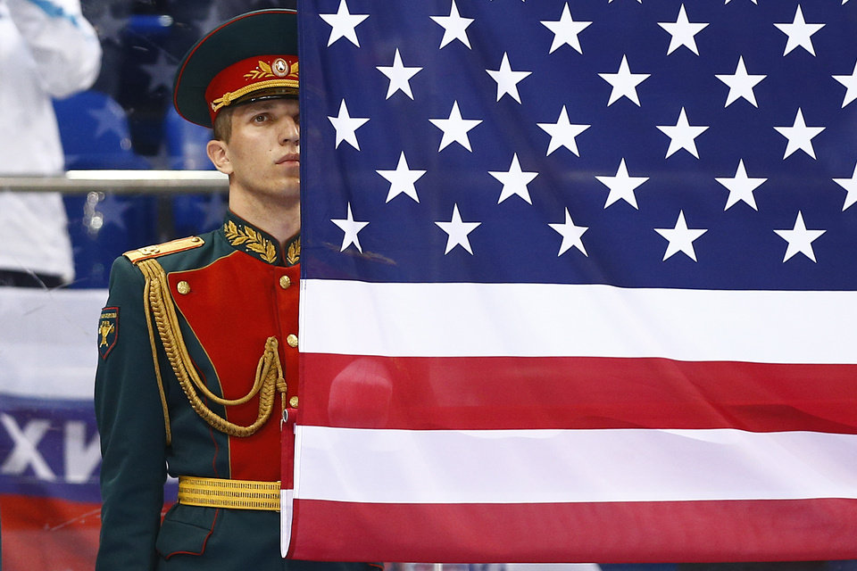 Photo - A Russian honor guard soldier stands behind the United States flag after the gold medal ice sledge hockey match between United States and Russia at the 2014 Winter Paralympics in Sochi, Russia, Saturday, March 15, 2014. United States won 1-0. (AP Photo/Pavel Golovkin)