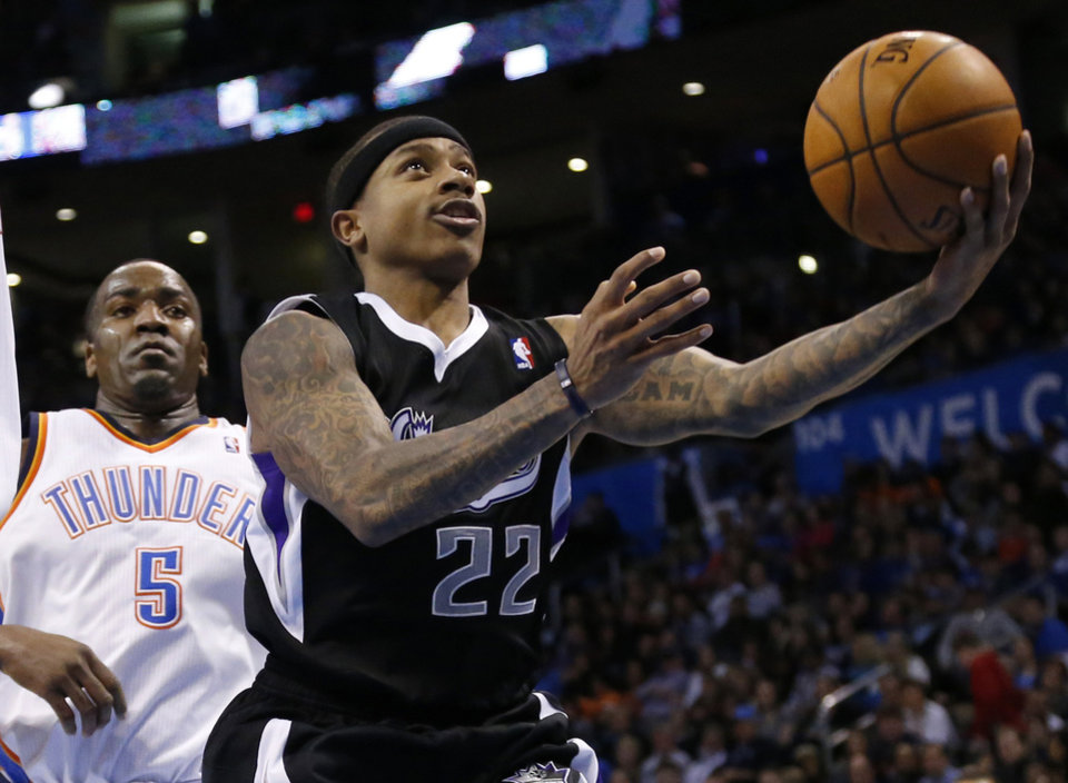 Photo - Sacramento Kings guard Isaiah Thomas (22) shoots in front of Oklahoma City Thunder center Kendrick Perkins (5) in the second quarter of an NBA basketball game in Oklahoma City, Sunday, Jan. 19, 2014. (AP Photo/Sue Ogrocki)