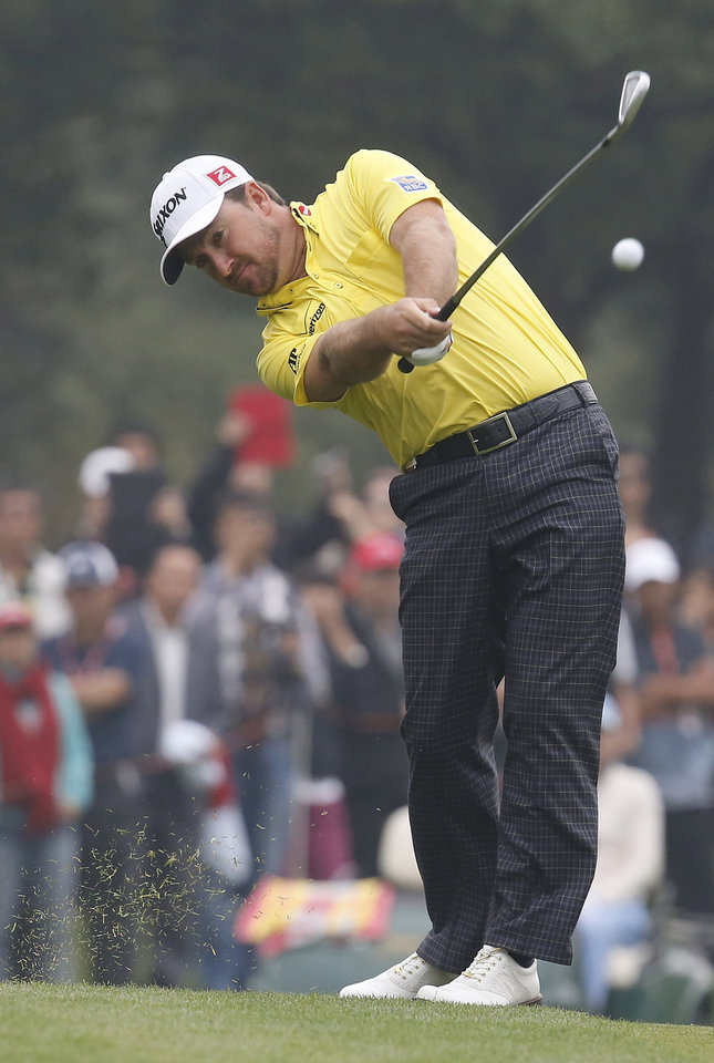 Photo - Graeme McDowell of Northern Ireland hits a ball from 9th fairway during the final round of the HSBC Champions golf tournament at the Sheshan International Golf Club in Shanghai, China, Sunday, Nov. 3, 2013.  (AP Photo/Eugene Hoshiko)