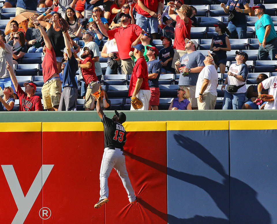 Photo - Miami Marlins Marcell Ozuna can't get to  Atlanta Braves Evan Gattis' a solo home run  during the second inning of a baseball game in Atlanta on Sunday, Aug. 31, 2014. (AP Photo/Atlanta Journal-Constitution, Curtis Compton)  MARIETTA DAILY OUT; GWINNETT DAILY POST OUT; LOCAL TELEVISION OUT; WXIA-TV OUT; WGCL-TV OUT