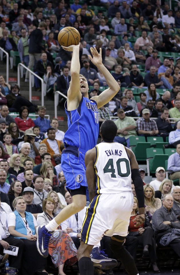 Photo - Dallas Mavericks' Dirk Nowitzki, left, shoots as Utah Jazz's Jeremy Evans (40) looks on in the second quarter during an NBA basketball game Wednesday, March 12, 2014, in Salt Lake City. (AP Photo/Rick Bowmer)