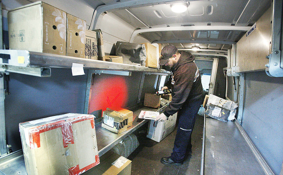 FedEx courier Chris Bernier scans a package while loading his truck at the FedEx facility at 4220 N Santa Fe in Oklahoma City. Photo by PAUL B. SOUTHERLAND, The Oklahoman