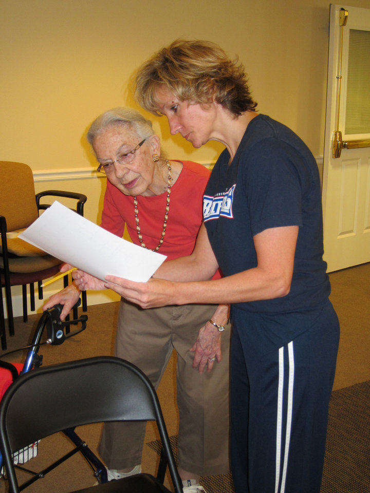 Joan Gibson, left, and Becky Major look over test results during Touchmark at Coffee Creek\'s Senior Fitness Testing, open to the community in observance of International Active Aging Week.