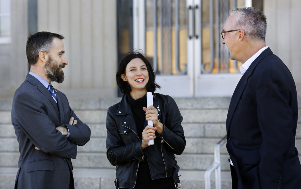 Photo -  Ryan Kiesel, left, smiles Tuesday while talking with Kylie Sheeley, center, and Bryan Newell after they and about two dozen supporters of Tondalao Hall's cause emerged from the Pottawatomie County Courthouse in Shawnee. Kiesel is executive director for American Civil Liberties Union of Oklahoma. Newell is the group's operations manager. [Photo by Jim Beckel, The Oklahoman]