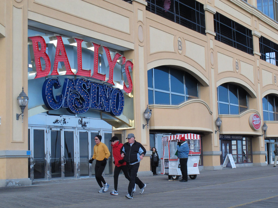 Joggers run on the Atlantic City N.J. Boardwalk on Feb. 6, 2013, a day before New Jersey Gov. Chris Christie vetoed a bill that would have allowed Internet gambling in his state. But Christie said he would sign a future bill that sets a 10-year trial period for Internet gambling, and increases the tax rate casinos would pay on their online winnings to 15 percent. (AP Photo/Wayne Parry)