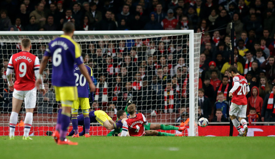 Photo - Arsenal's Mathieu Flamini, right, scores an own goal to make the final score 2-2 during the English Premier League soccer match between Arsenal and Swansea City at the Emirates Stadium in London, Tuesday, March 25, 2014. (AP Photo/Matt Dunham)