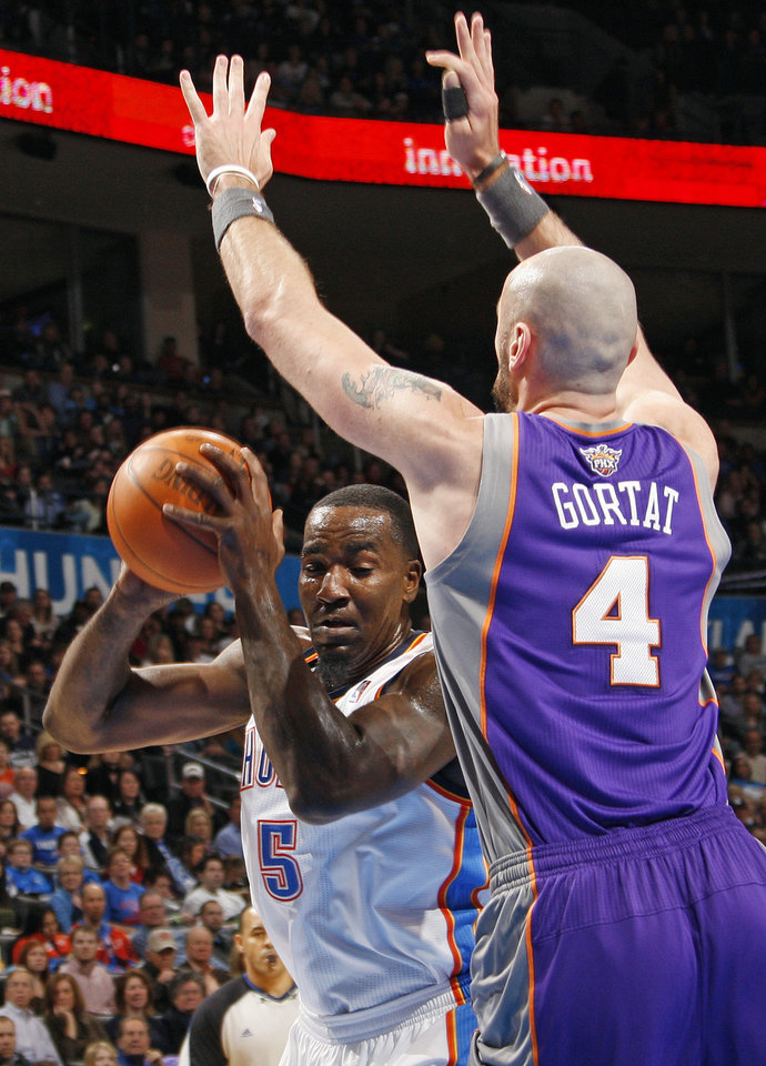 Photo - Oklahoma City's Kendrick Perkins (5) works around the defense of Phoenix's Marcin Gortat (4) during the NBA basketball game between the Oklahoma City Thunder and Phoenix Suns at Chesapeake Energy Arena in Oklahoma City, Saturday, Dec. 31, 2011. Photo by Nate Billings, The Oklahoman