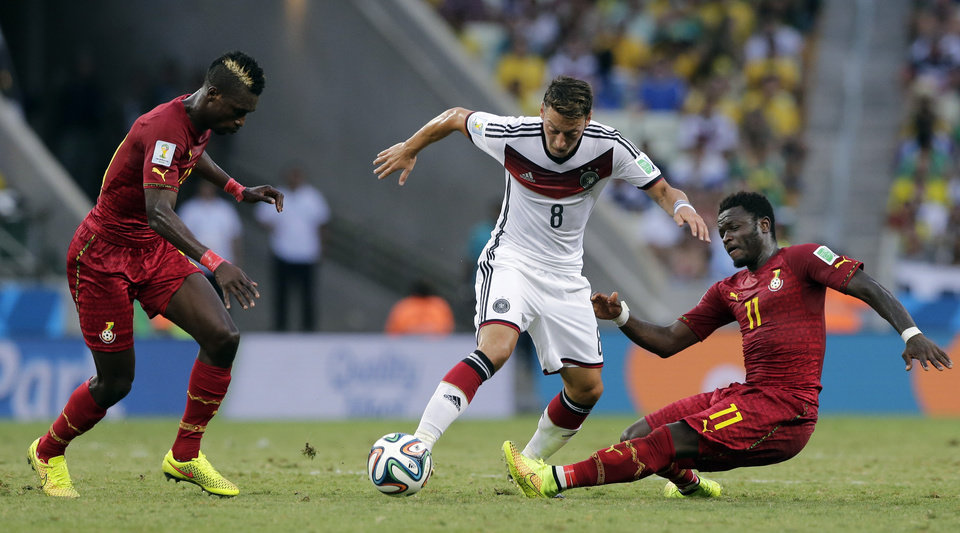 Photo - Germany's Mesut Ozil, center, is challenged by Ghana's Sulley Muntari, right, during the group G World Cup soccer match at the Arena Castelao in Fortaleza, Brazil, Saturday, June 21, 2014. (AP Photo/Matthias Schrader)