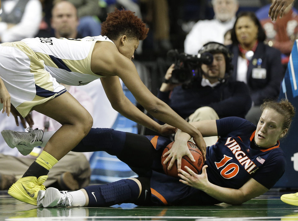 Photo - Georgia Tech's Aaliyah Whiteside, left, reaches in as Virginia's Kelsey Wolfe, right, falls with the ball during the second half of an NCAA college basketball game at the Atlantic Coast Conference tournament in Greensboro, N.C., Thursday, March 6, 2014. Georgia Tech won 77-76. (AP Photo/Chuck Burton)