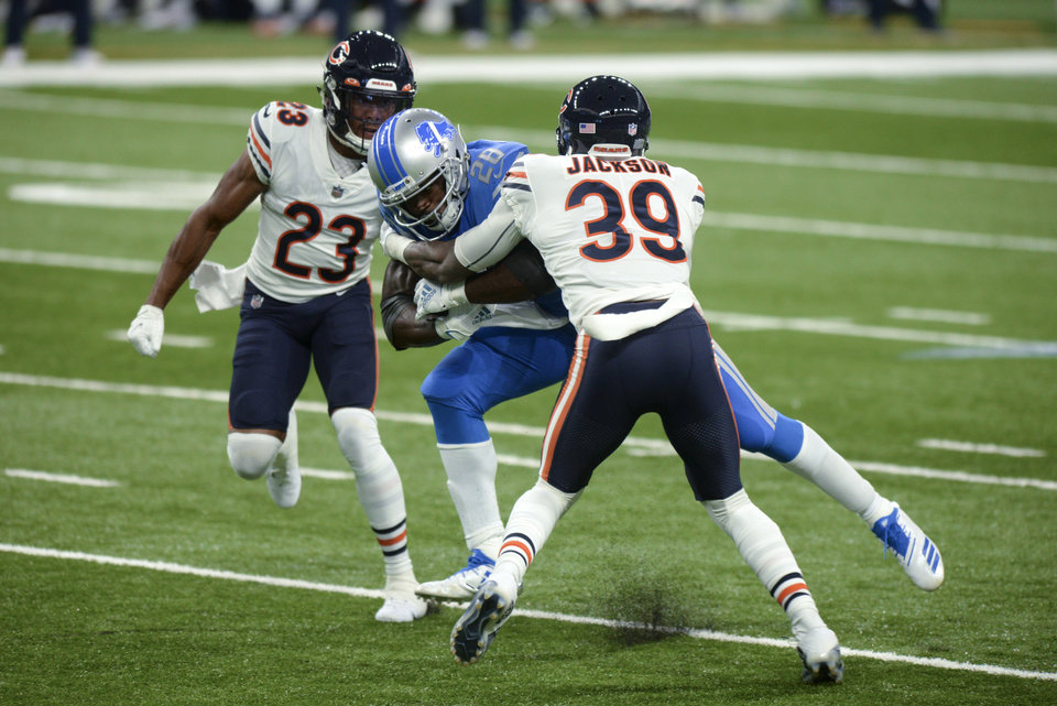 Photo - Detroit Lions running back Adrian Peterson (28) runs between Chicago Bears free safety Eddie Jackson (39) and cornerback Kyle Fuller (23) in the first half of an NFL football game in Detroit, Sunday, Sept. 13, 2020. (AP Photo/Jose Juarez)
