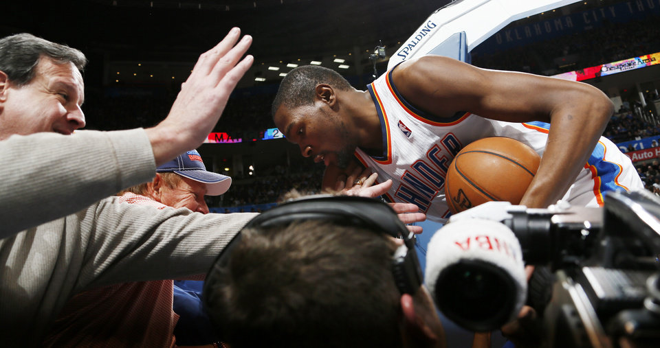 Photo - Oklahoma City's Kevin Durant (35) falls into photographers during an NBA basketball game between the Oklahoma City Thunder and Minnesota Timberwolves at Chesapeake Energy Arena in Oklahoma City, Friday, Feb. 22, 2013. Oklahoma City won, 127-111. Photo by Nate Billings, The Oklahoman