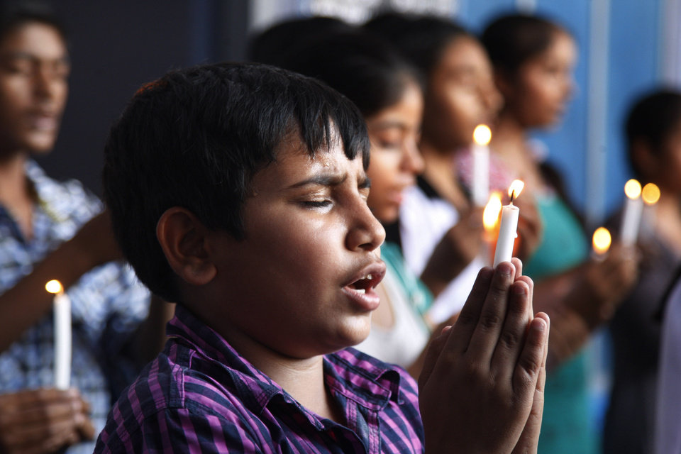 Photo - Indian students  hold a candles and pray for the victims of Uttarakhand floods, in Jammu, India, Friday, June 21, 2013. The Indian air force is dropping paratroopers, food packets and medicine for tens of thousands of people trapped in up to 100 inaccessible towns and villages in northern Himalayas devastated by heavy monsoon rains and landslides over the weekend and more than hundred people are killed. (AP Photo/Channi Anand)