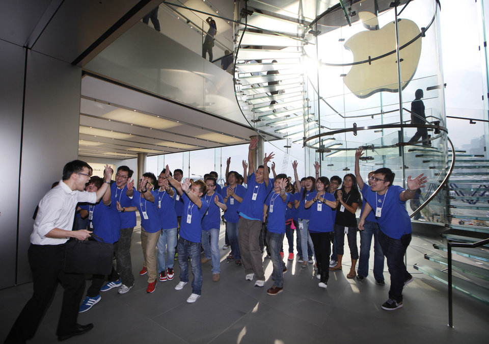Photo -   A customer cheers with staff members of Apple Inc. as the Apple store in Hong Kong started selling iPhone 5 Friday, Sept. 21, 2012. Apple's Asian fans jammed the tech juggernaut's shops in Australia, Hong Kong, Japan and Singapore to pick up the latest version of its iPhone. (AP Photo/Kin Cheung)