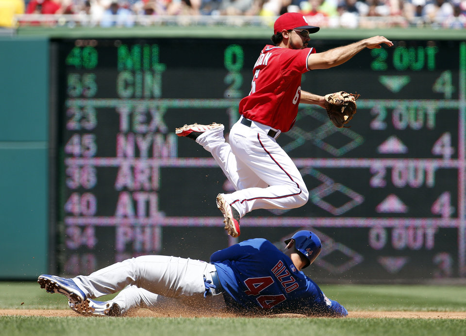 Photo - Washington Nationals second baseman Anthony Rendon, top, jumps over Chicago Cubs' Anthony Rizzo, who was out, but is unable to get Cubs' Starlin Castro out at first base during the third inning of a baseball game at Nationals Park, Sunday, July 6, 2014, in Washington. (AP Photo/Alex Brandon)