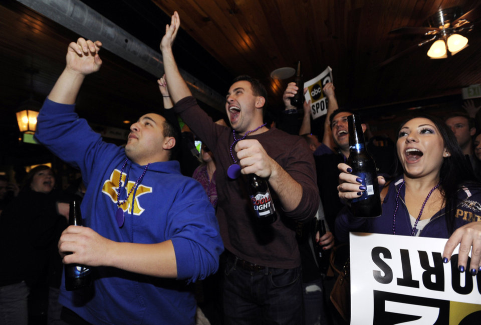 Photo - From left, Baltimore Ravens fans Nicholas Giorgi, Cameron Schmiemann and Courtney East react to a Ravens touchdown against the New England Patriots while watching a televised broadcast of the AFC Championship NFL football game, Sunday, Jan. 20, 2013, in Baltimore. The Ravens won 28-13. (AP Photo/Gail Burton)