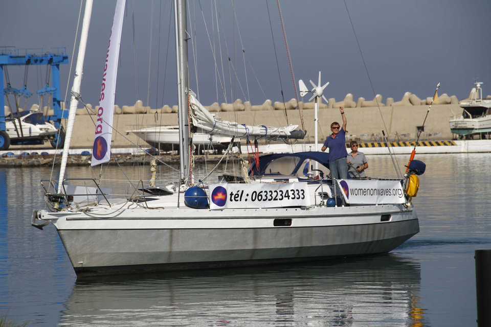 "Women's rights activists sail a small boat around a yacht harbor in Smir, northern Morocco on Thursday Oct 4 2012 to raise awareness about safe abortions, despite officials� efforts to seal the port and anti-abortion protests on land. Organizers had initially said a large ship offering abortion information and services was on its way from the Netherlands on Thursday. In response, police sealed the port for what it called �military maneuvers� and denied journalists access. But in the afternoon, organizers admitted that they already had stationed a sailboat in the port several days ago, fearing that authorities would close the port. And that sailboat took off around the harbor bearing banners. Meanwhile, on land, about 200 protesters targeted the activists from ""Women on Waves,"" the Dutch organization behind the boat. (AP Photo/Paul Schemm)."