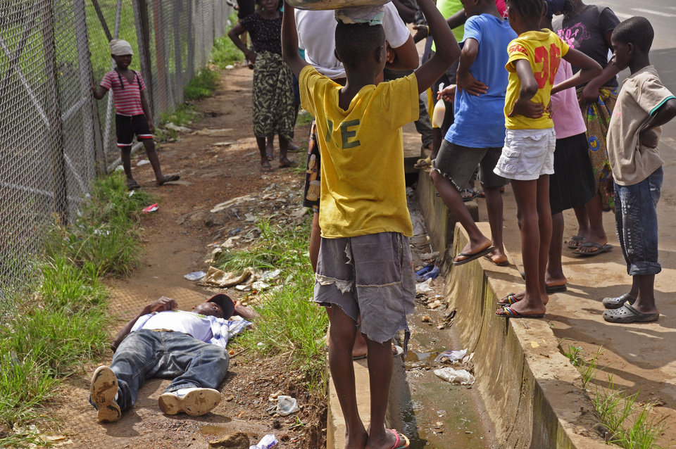 Photo - Children surround a man, left, that fell down while walking on a street suspected of having contracted the Ebola virus in the city of Monrovia, Liberia, Tuesday, Aug. 19, 2014. The World Health Organization says the outbreak has killed more than 1,200 people, while authorities struggle to contain its spread and treat the sick. (AP Photo/Abbas Dulleh)