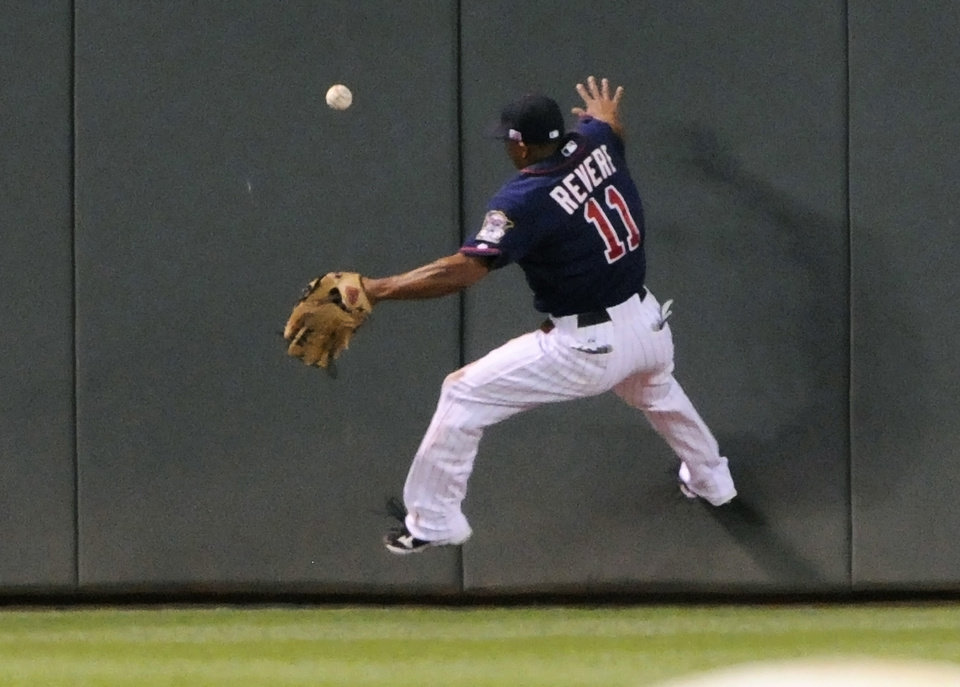 Photo -   Minnesota Twins center fielder Ben Revere goes up the wall to chase a triple off the bat of Kansas City Royals' Alex Gordon in the third inning of a baseball game, Tuesday, Sept. 11, 2012, in Minneapolis. (AP Photo/Jim Mone)