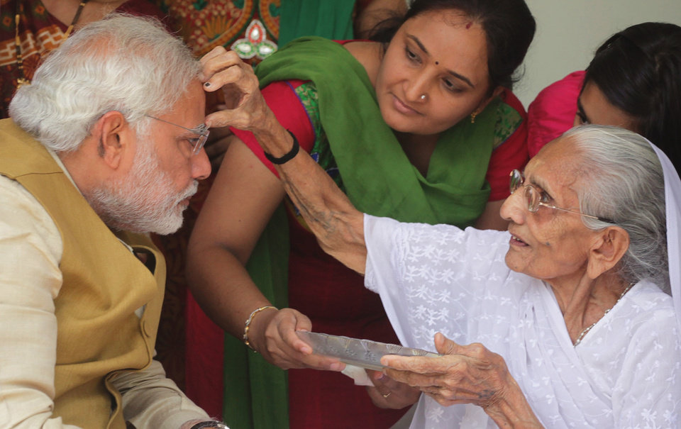 Photo - 90-year-old Hiraben marks the forehead of her son and India's next prime minister Narendra Modi with vermillion as a sign of blessing in Gandhinagar, in the western Indian state of Gujarat, Friday, May 16, 2014. The top official in Gujarat state for over a decade, Modi often contrasted his humble roots with the posh background of his main rival, 43-year-old Rahul Gandhi, heir to India's most powerful political dynasty. As the career politician led his party through a dazzling, high-tech election campaign, Modi called voters' attention to his mother riding a three-wheeled auto-rickshaw to cast her ballot earlier this month.