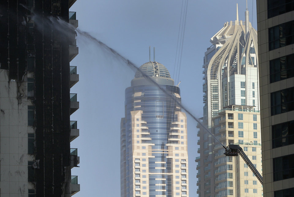 Photo -   Firefighters spray water on Tamweel residential tower after a fire gutted portions of the building at Jumeirah Lakes Towers, in Dubai, United Arab Emirates, Sunday, Nov. 18, 2012. Civil defense officials did not give immediate details on possible casualties or the cause of the predawn fire. (AP Photo/Kaveh Kashani)