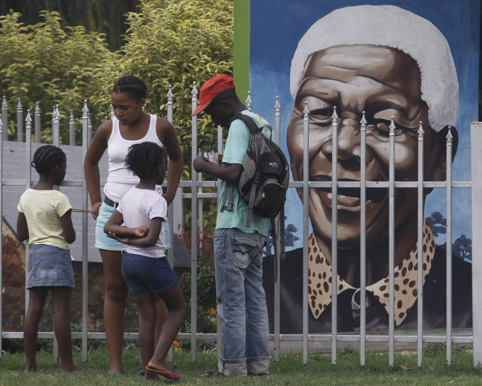 Photo - Visitors gather in front of a portrait of former president Nelson Mandela, in a Park in Soweto, South Africa, Thursday, March, 28, 2013. 94-year-old Mandela, the anti-apartheid leader who became South Africa's first black president, has been hit by a lung infection again and is in a hospital, the presidency said. Mandela, has become increasingly frail in recent years and has been hospitalized several times in recent months, including earlier this month when he underwent what authorities said was a scheduled medical test. The Nobel laureate is a revered figure in South Africa, which has honored his legacy of reconciliation by naming buildings and other places after him and printing his image on national banknotes. (AP Photo/Denis Farrell)