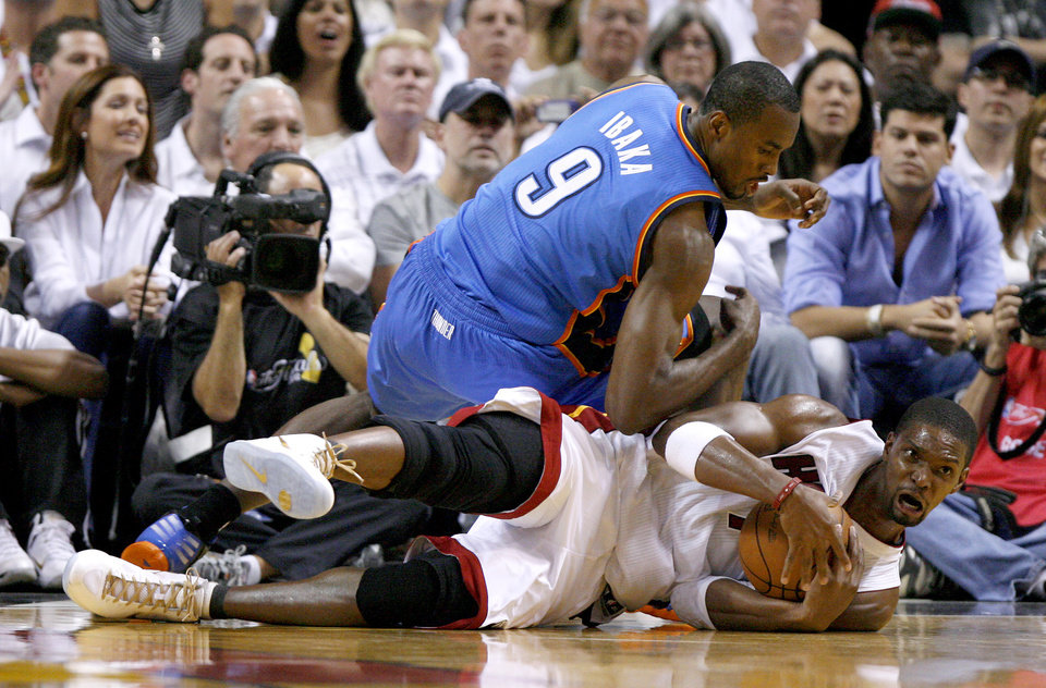 Miami's Chris Bosh (1) gains control of the ball as Oklahoma City's Serge Ibaka (9) lands on top of him during Game 4 of the NBA Finals between the Oklahoma City Thunder and the Miami Heat at American Airlines Arena, Tuesday, June 19, 2012. Photo by Bryan Terry, The Oklahoman