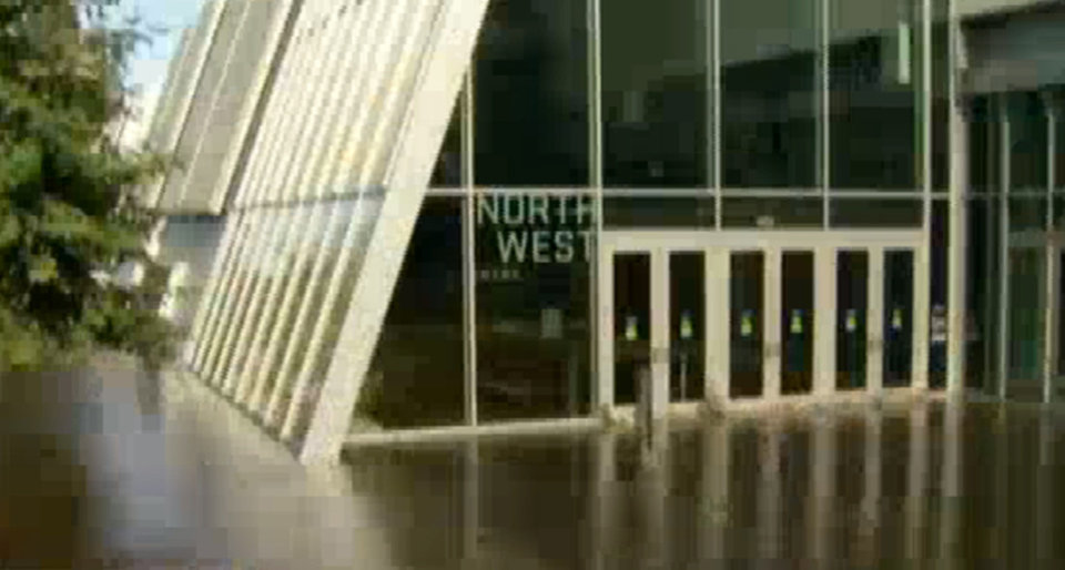 Photo - In this photo taken from video provided by nbc4la.com, water reaches the main entry doors to Pauley Pavilion, home of UCLA basketball, after a 30-inch water main burst on nearby Sunset Boulevard Tuesday, July 29, 2014, in Los Angeles. (AP Photo/nbc4la.com) MANDATORY CREDIT