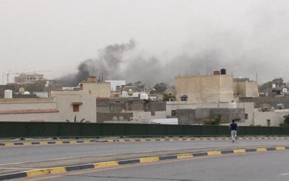 Photo - In this image made from video provided by the Libyan national army via AP Television, smoke rises over the parliament area after troops of Gen. Khalifa Hifter targeted Islamist lawmakers and officials at the parliament in Tripoli, Libya, Sunday, May 18, 2014. Forces loyal to a rogue Libyan general attacked the country's parliament Sunday, expanding his eastern offensive against Islamists into the heart of the country's capital. (AP Photo/Libyan national army)