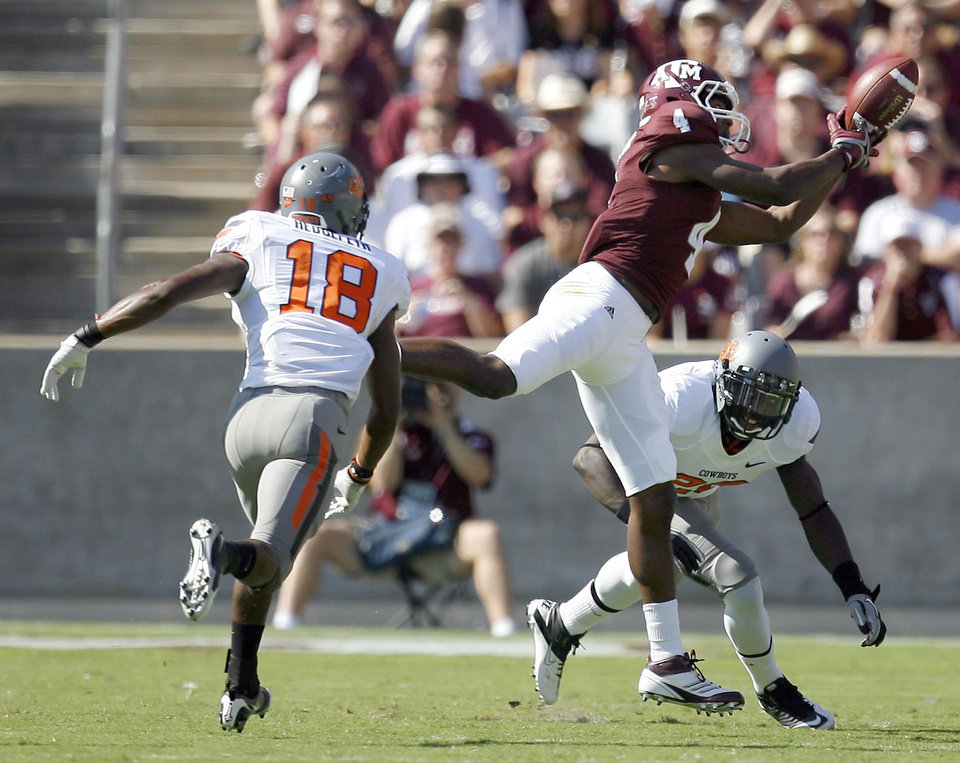 Texas A&M\'s Brandal Jackson makes a catch in front of in Oklahoma State\'s Devin Hedgepath and Deion Imade the first half of their game in College Station, Texas, on Saturday. Photo by Sarah Phipps, The Oklahoman