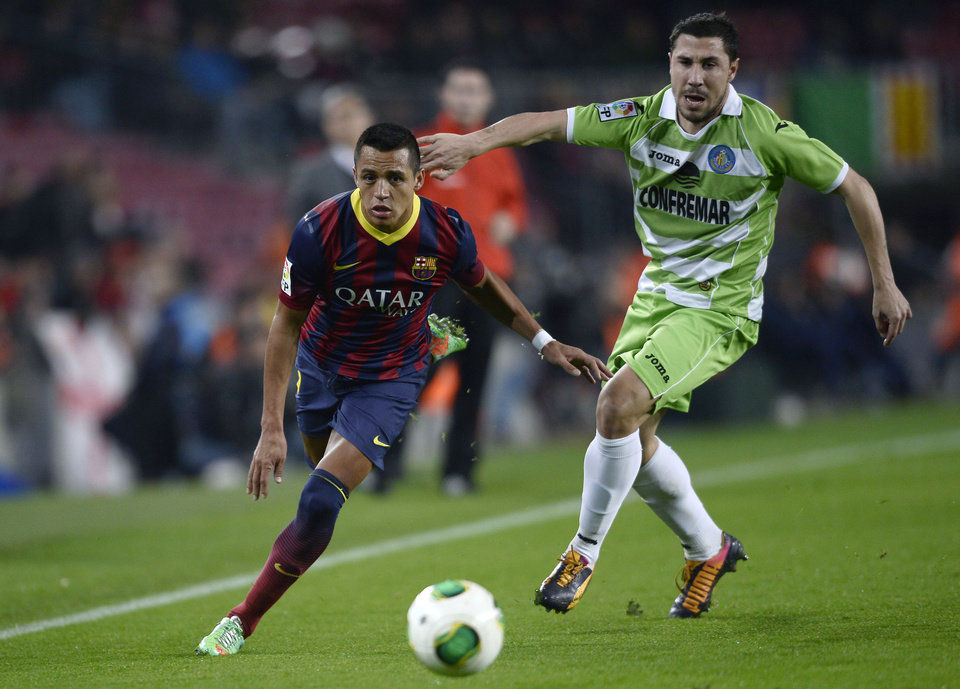 Photo - FC Barcelona's Alexis Sanchez, from Chile, left, duels for the ball against Getafe´s Albert Lopo during a Copa del Rey soccer match at the Camp Nou stadium in Barcelona, Spain, Wednesday, Jan. 8, 2014. (AP Photo/Manu Fernandez)