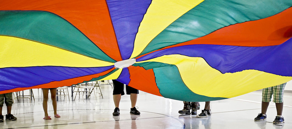 Photo - Campers wave the parachute during the Kids Rock Camp at Britton Christian Church in Oklahoma City.  Photos by Chris Landsberger, The Oklahoman
