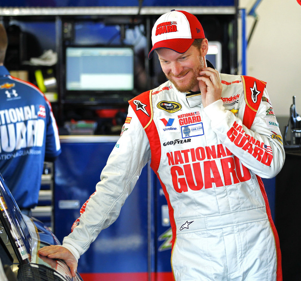 Photo - Driver Dale Earnhardt Jr. stands by his car in the garage before practice for the NASCAR Sprint Unlimited auto race at Daytona International Speedway in Daytona Beach, Fla., Friday, Feb. 14, 2014. (AP Photo/Terry Renna)