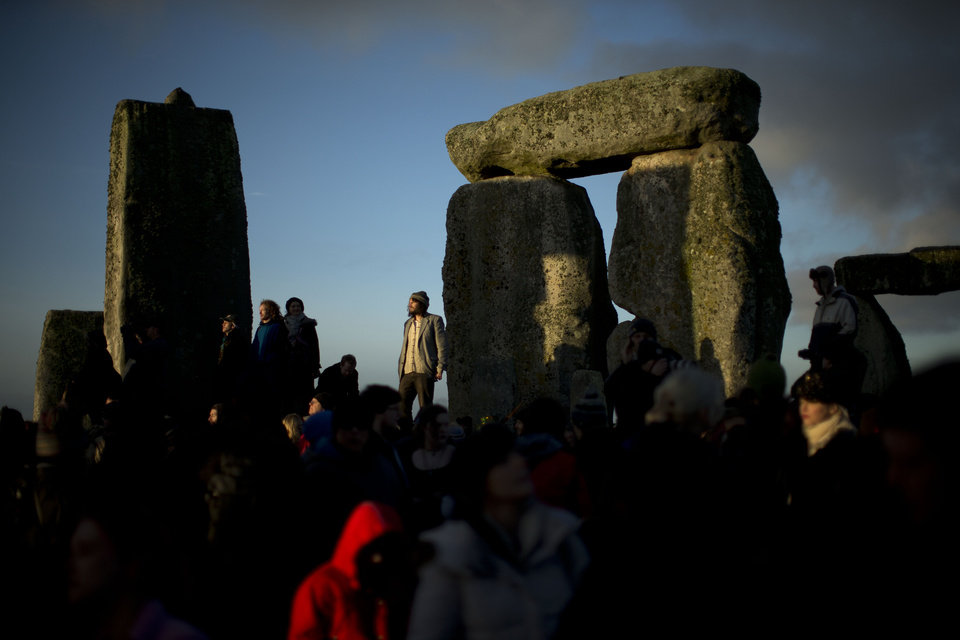 Photo - People soak up the sun after its rise at the ancient stone circle of Stonehenge, in southern England, as access to the site is given to druids, New Age followers and members of the public on the annual Winter Solstice, Friday, Dec. 21, 2012.  Doomsday hour is here and so still are we.  According to legend, the ancient Mayans' long-count calendar ends at midnight Thursday, ushering in the end of the world. Didn't happen.