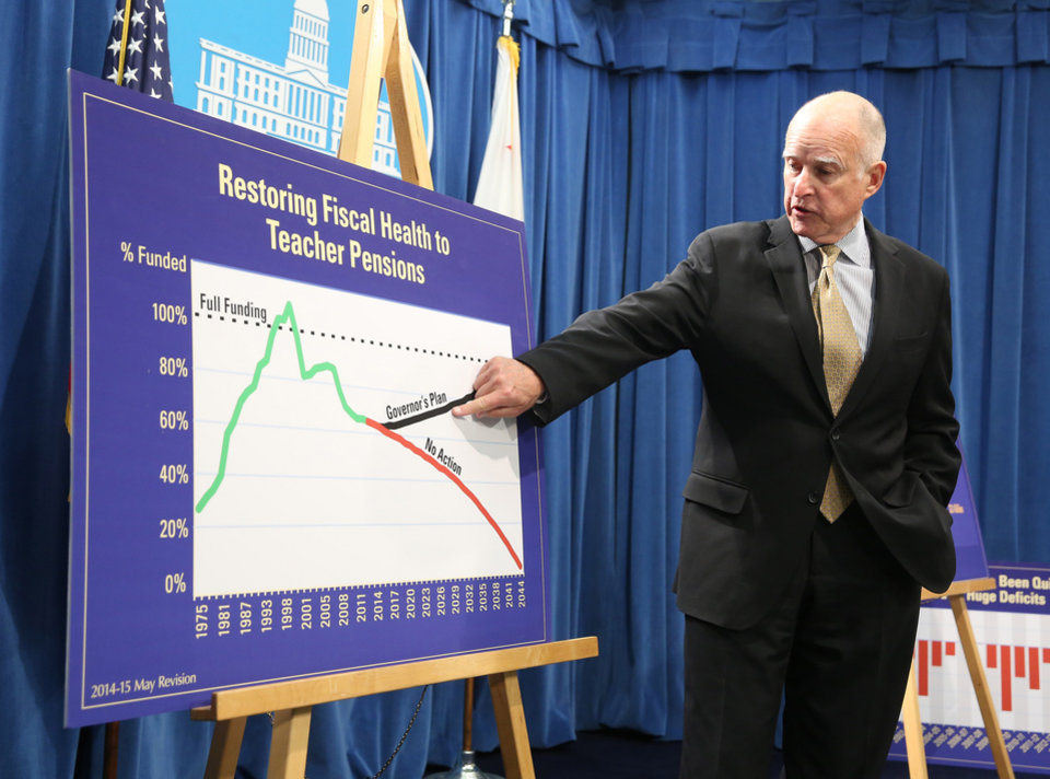 Photo - Gov. Jerry Brown points to a chart showing his plan to fund teacher pensions as he unveils his revised 2014-15 state budget at the Capitol in  Sacramento, Calif., Tuesday, May 13, 2014.  The revised budget projects $107.7 billion in spending from the general fund, that's nearly $1 billion more than the budget Brown proposed in January.(AP Photo)